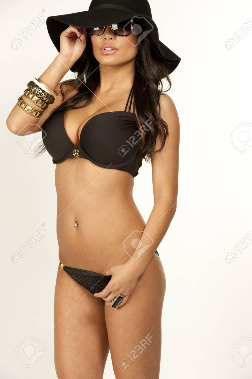 56a269717101 Un modelo de traje de baño japonés con un sombrero negro, gafas de sol y un  traje de baño de 2 piezas sobre un fondo blanco.