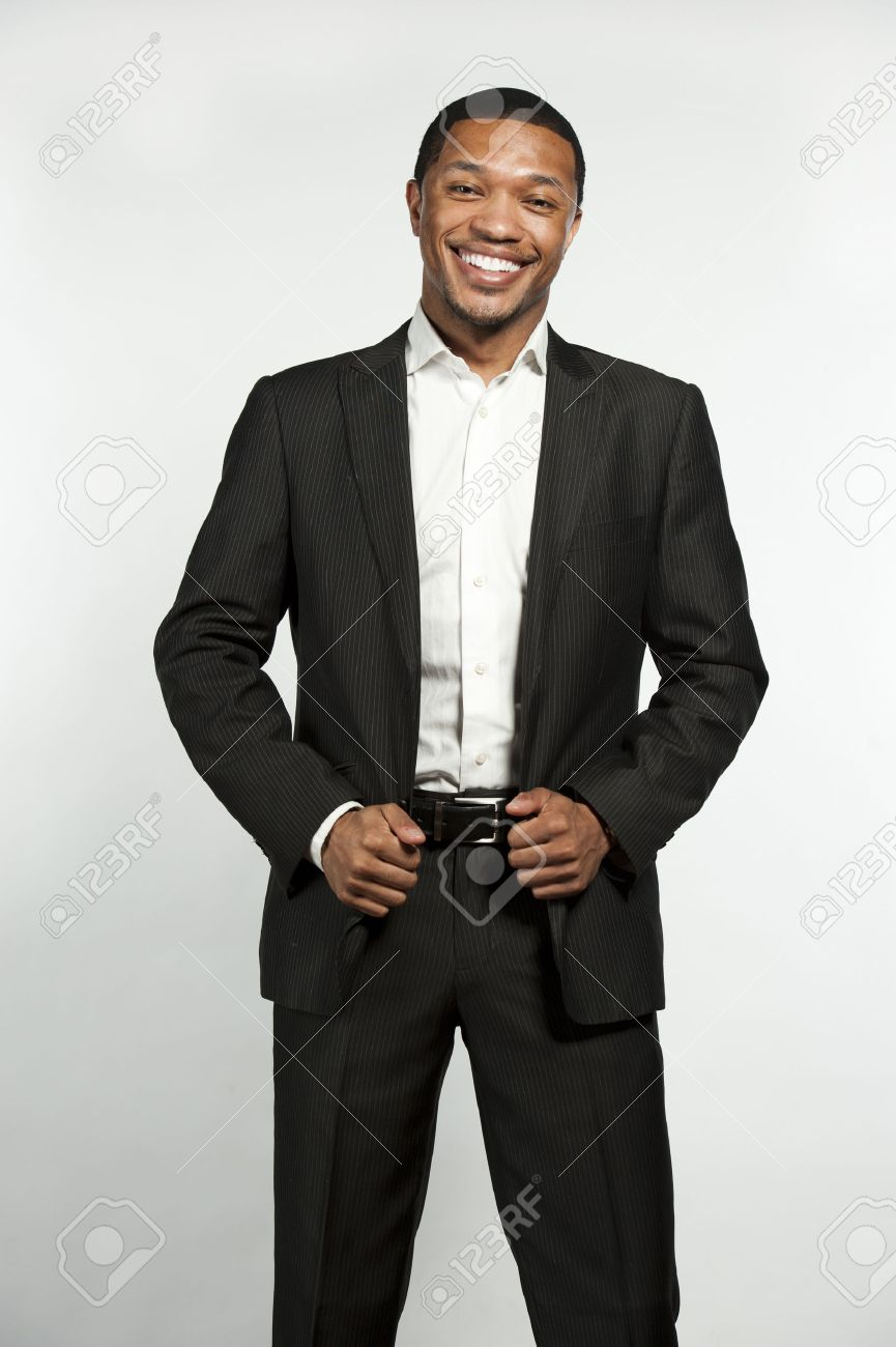 5d907f1c92 A young chic black male laughing while wearing white button down shirt with  a custom suit