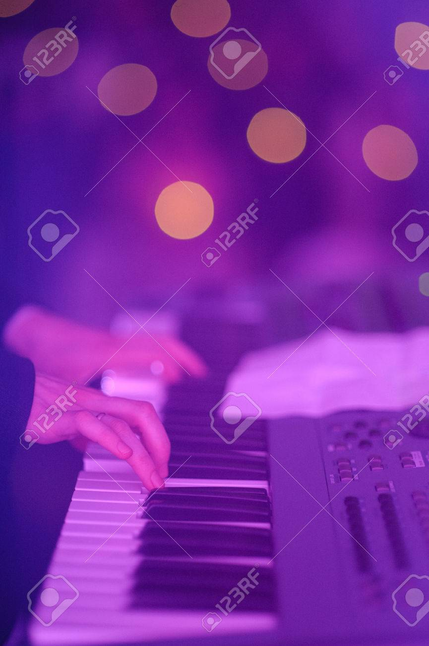 hands of musician playing keyboard in concert with shallow depth