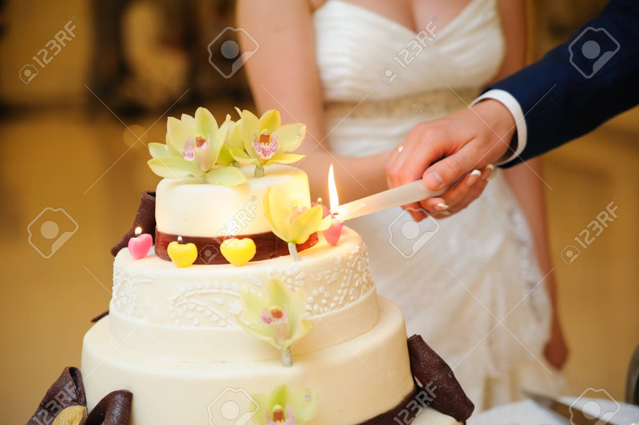 Bride And Groom Are Slicing The Wedding Cake On Reception Stock ...