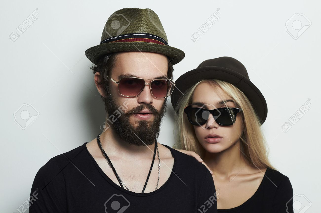 60cbb0710ba fashion beautiful couple in hat together. Hipster boy and girl. Bearded  young man and