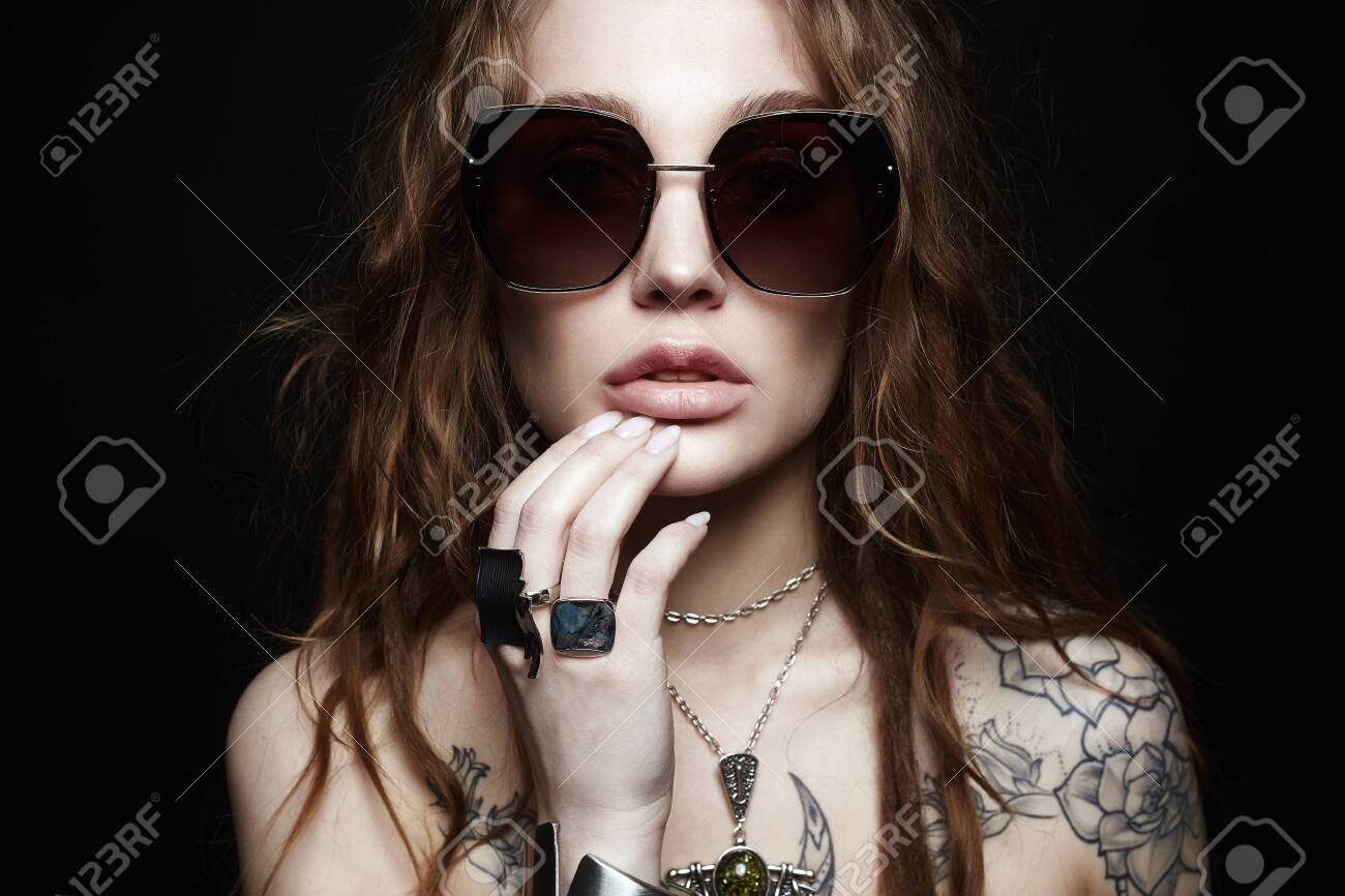 fashion portrait of Beautiful woman with tattoo. beauty tattooed girl in sunglasses and jewelry - 126969230