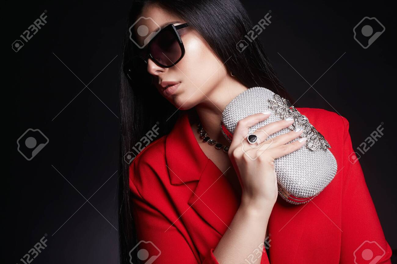 fashion portrait of Beautiful woman with clutch bag and sunglasses.jewelry