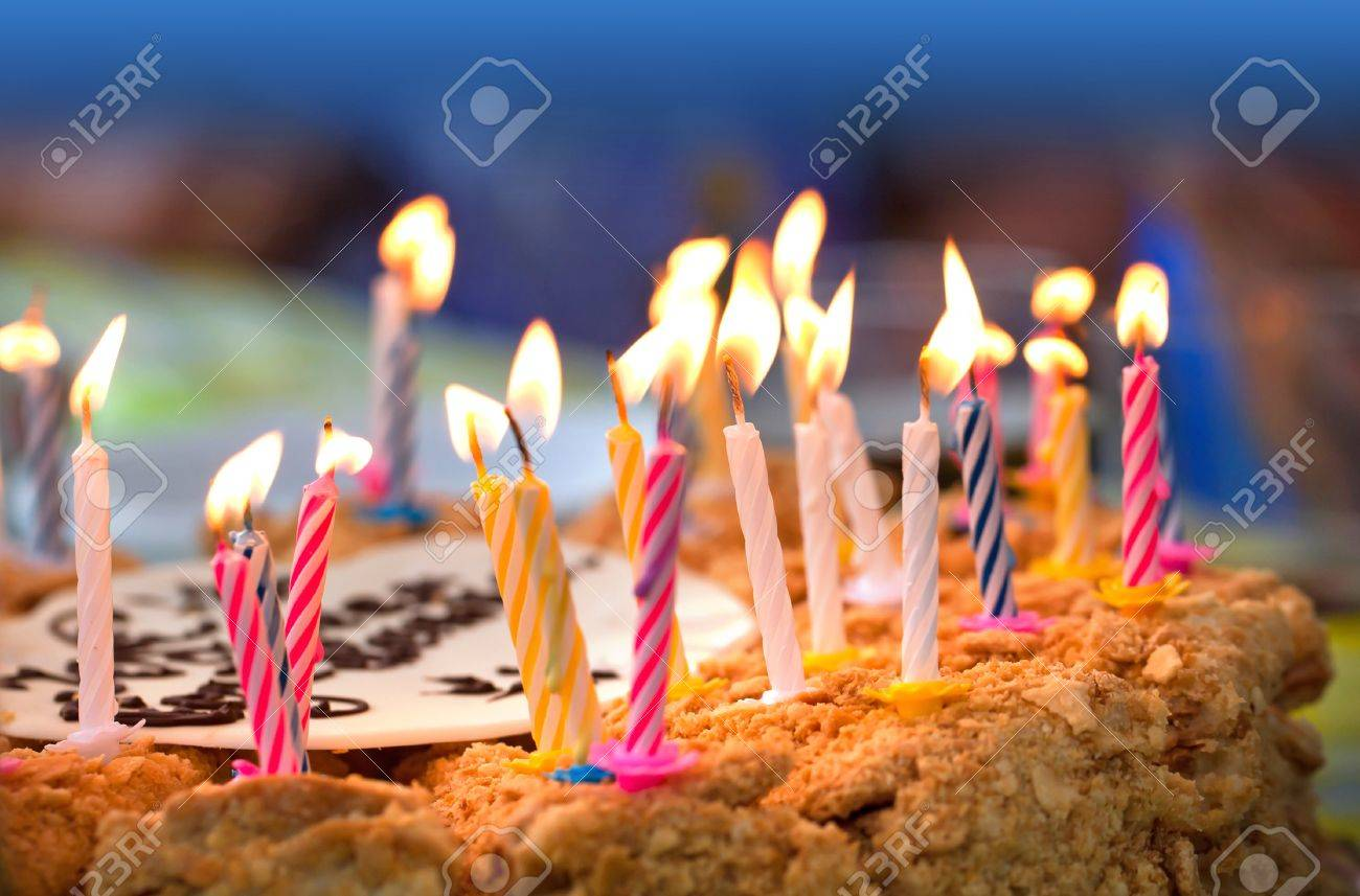 Colorful Candles On Birthday Cake Above Dark Background Stock Photo