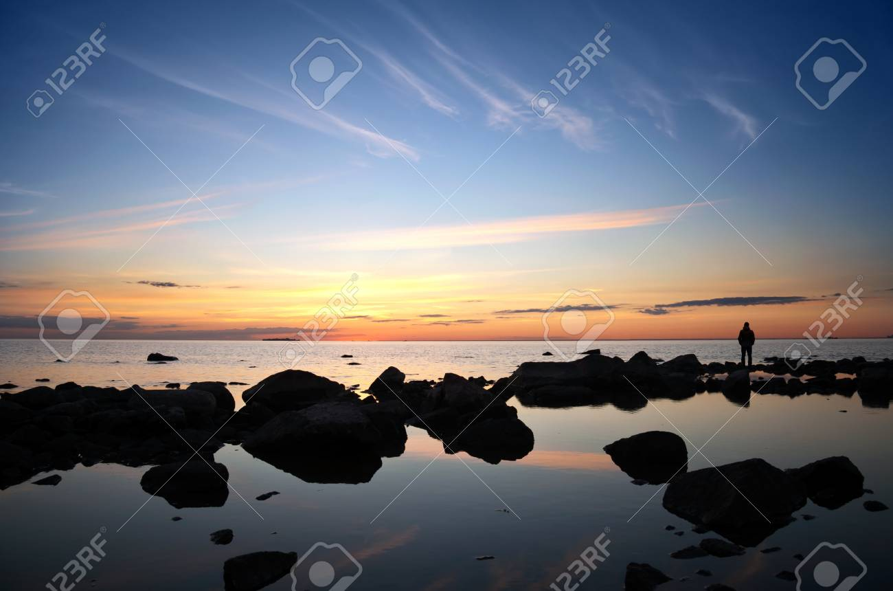 A man on the coastal stones starring at the bright sunset over the sea Stock Photo - 15658825