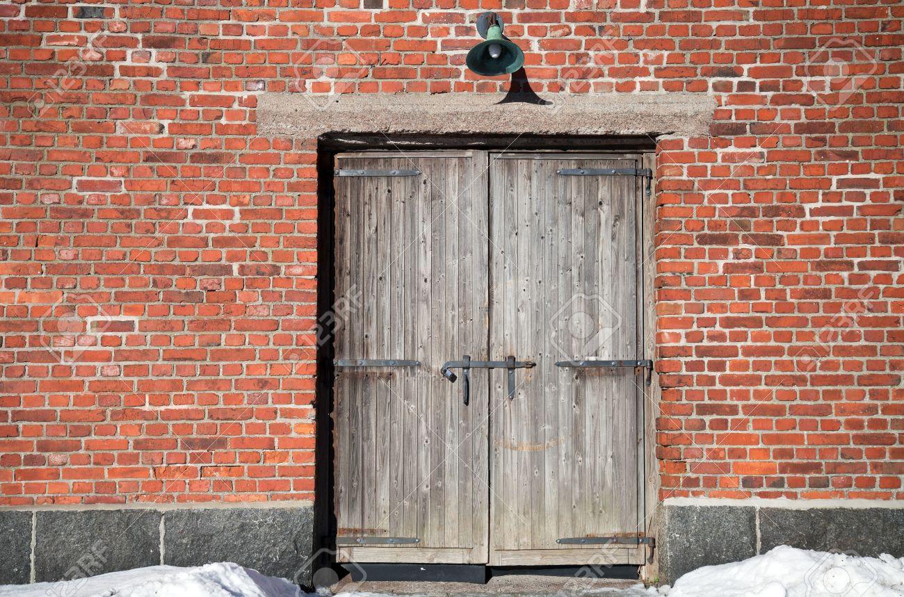 Vieux Portail En Bois mur de briques d'un immeuble ancien avec le vieux portail en bois surmonté