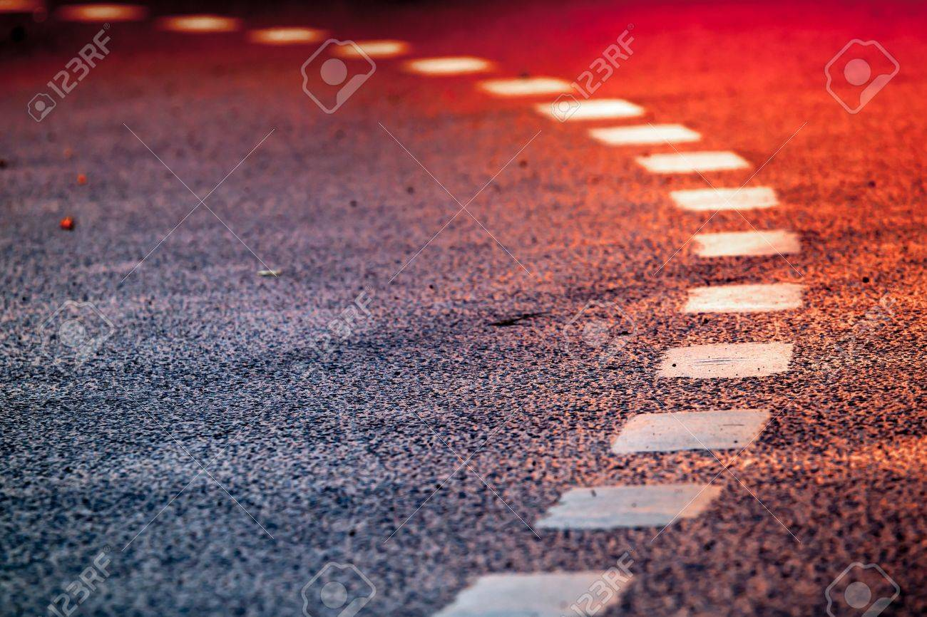 Turning asphalt road with marking lines and bright red reflections Stock Photo - 16004082