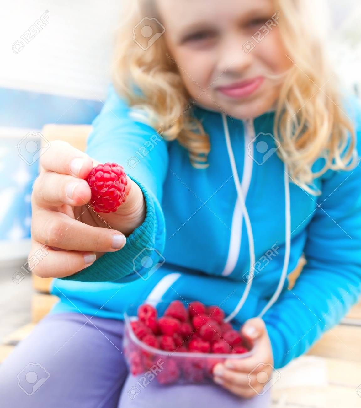 Little blond active girl held out fresh raspberry from his full box. Outdoor portrait with selective focus on berry Stock Photo - 16404810