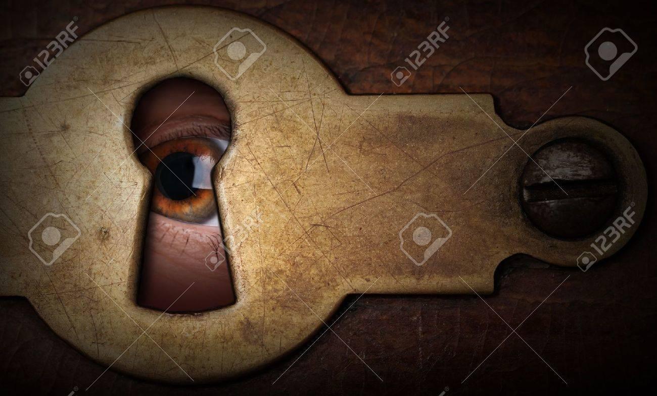 Brown eye looking through a vintage metal keyhole - 17370161