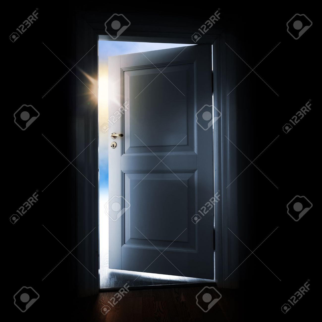 opening blue door in a dark room with shining light and sky outside stock photo opening69 light