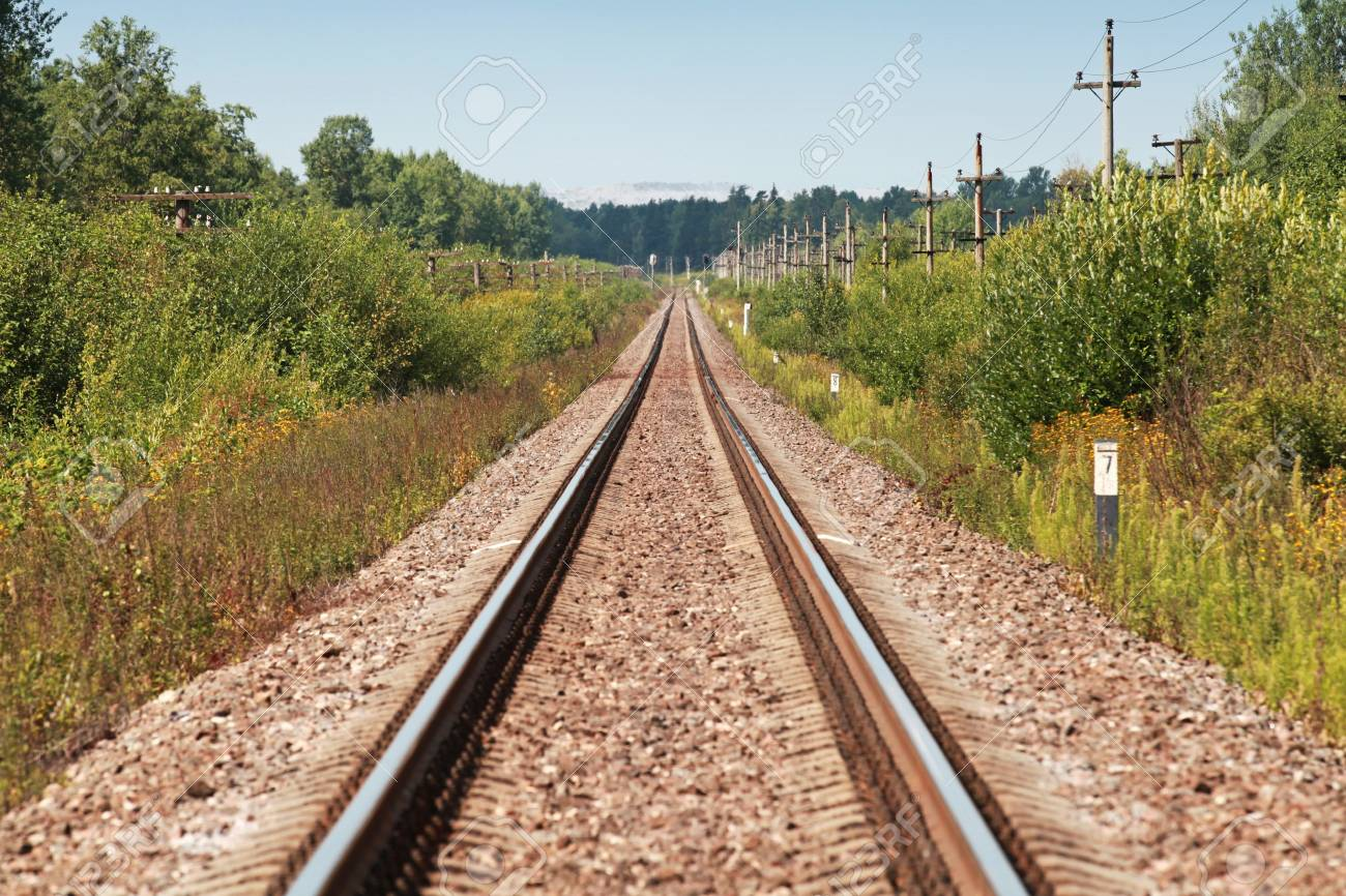 Long straight railway perspective with poles, green grass and blue sky Stock Photo - 21780925