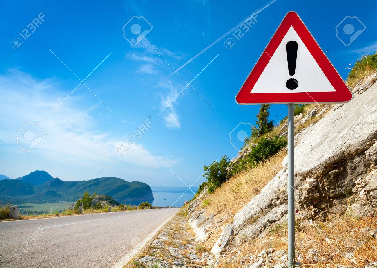 Warning road sign with an exclamation mark in red triangle on mountain highway - 22425557