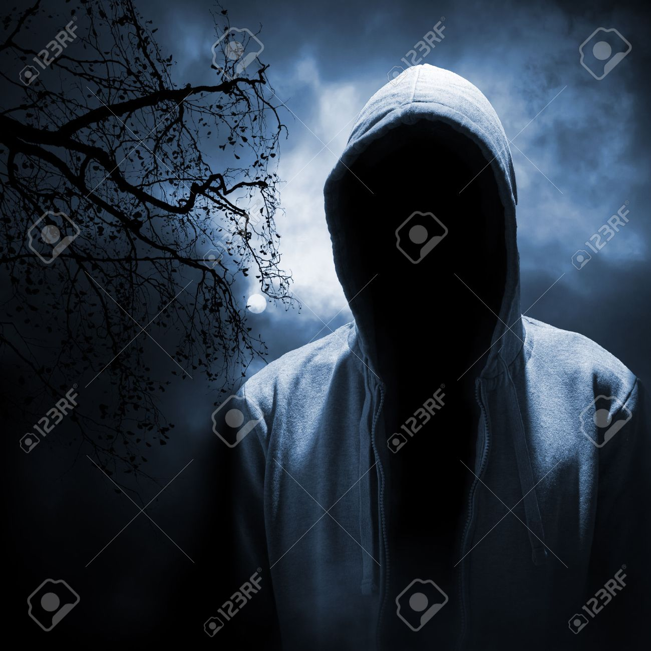 dangerous man hiding under the hood in the dark night forest stock
