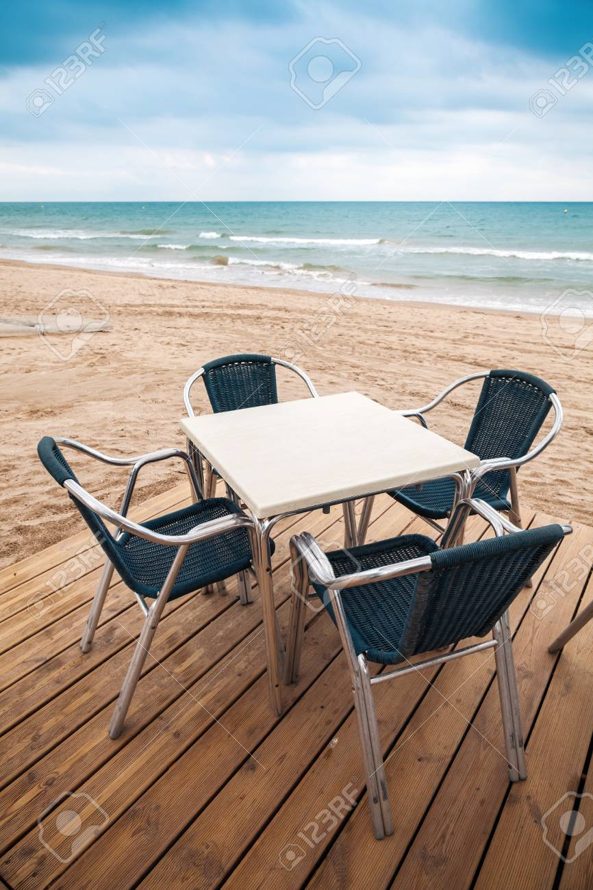 Open Space Sea Side Bar Interior With Wooden Floor And Metal Armchairs On  The Sandy Beach