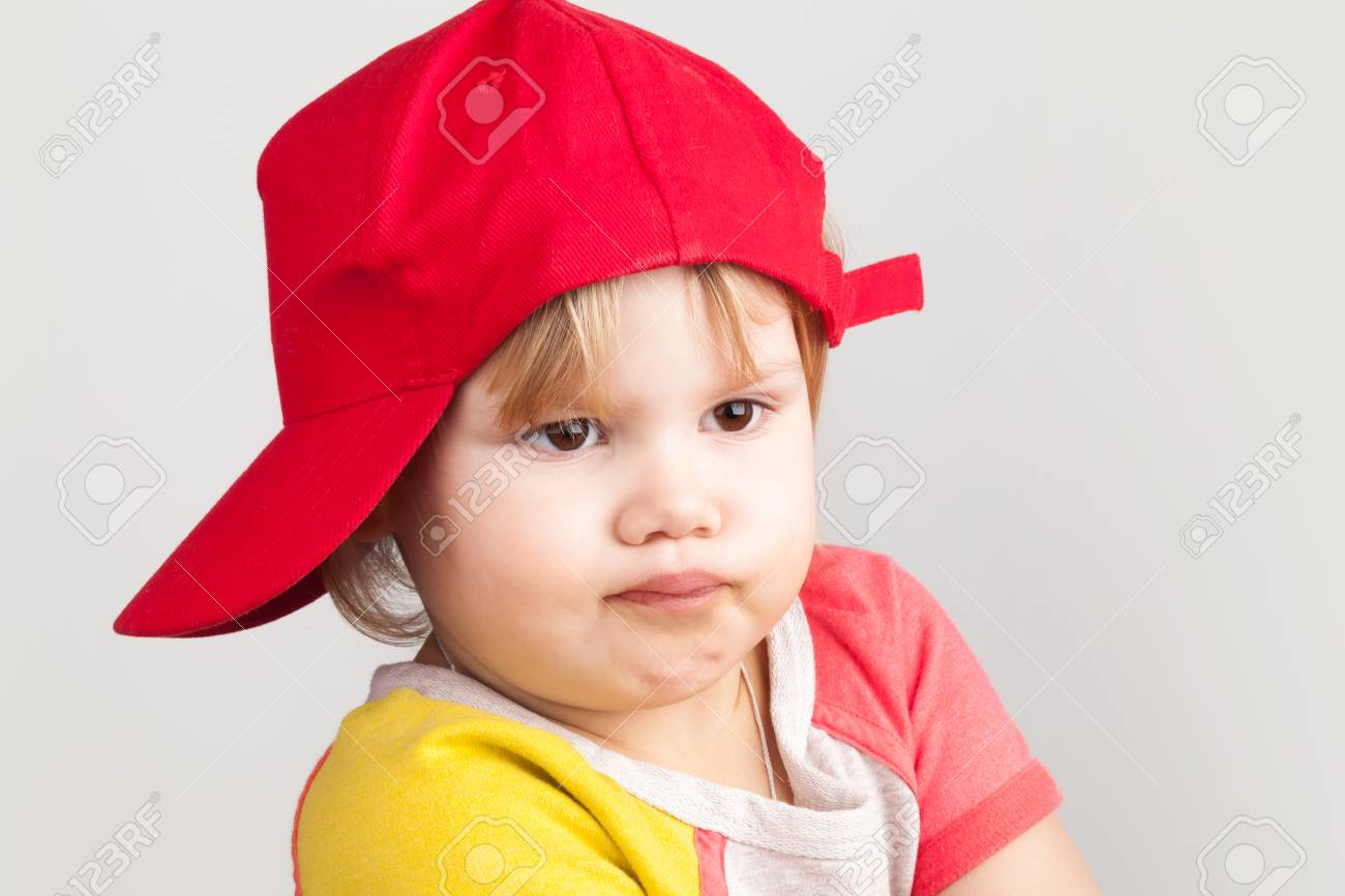 18bd6c649 Studio portrait of funny confused baby girl in red baseball cap..