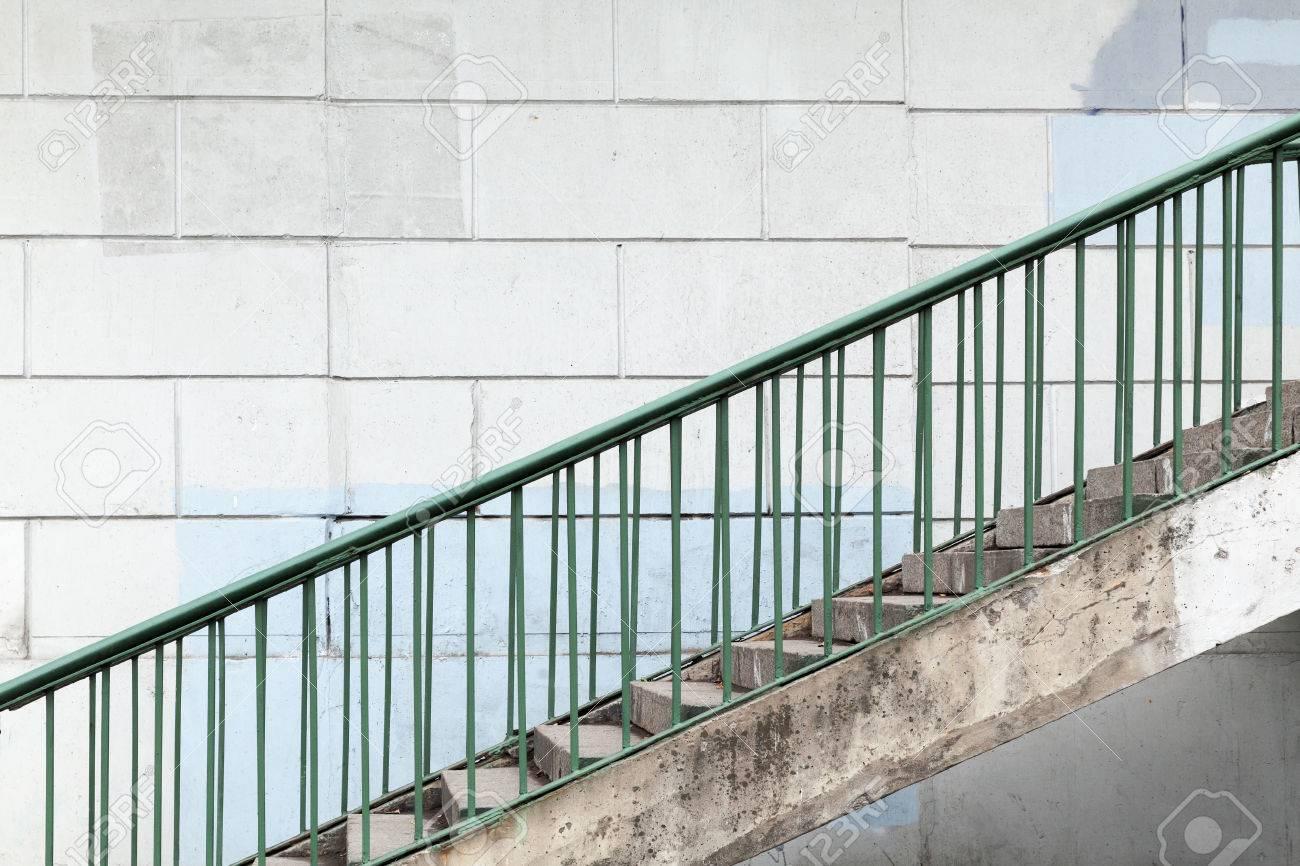escalera urbana con barandas de metal verde sobre la pared de hormign blanco foto de archivo
