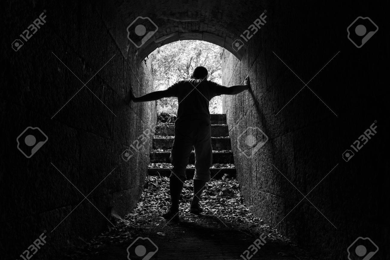 Stock photo young tired man leaves dark stone tunnel with glowing end black and white photo