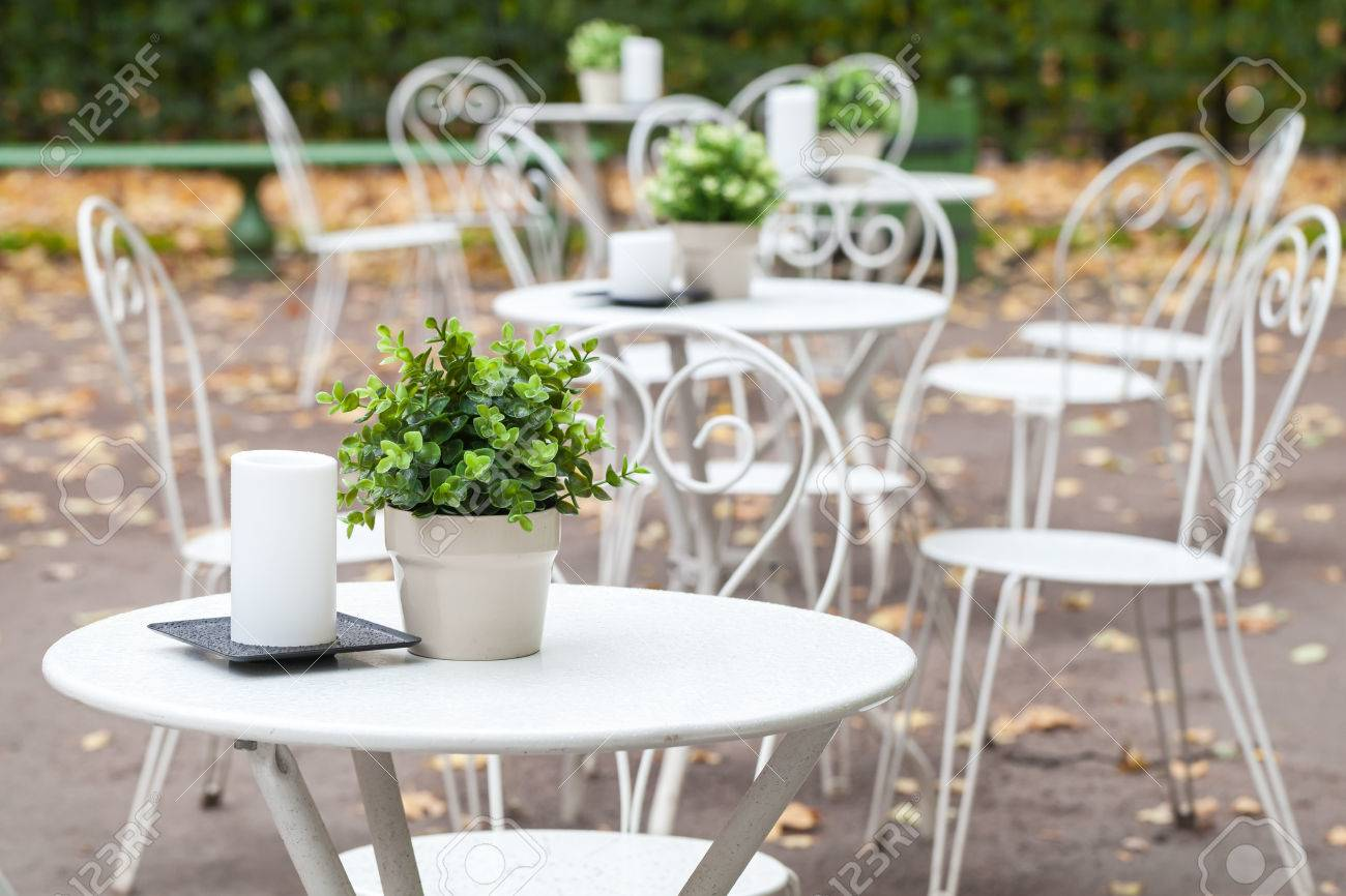 Outdoor Cafeteria Background Interior, Metal White Chairs And Tables With  Decorative Green Plants In Pots