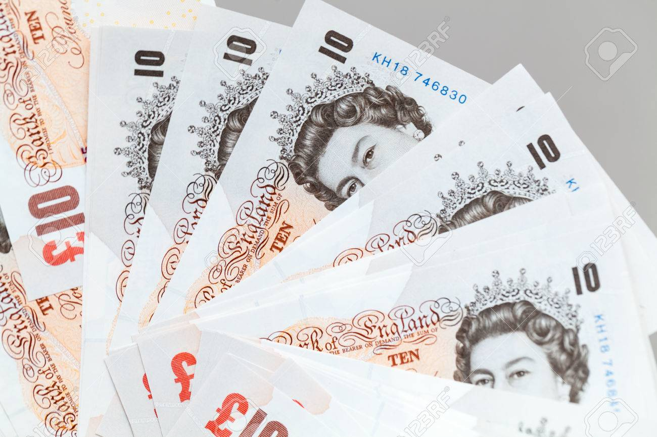 Ten pound notes of the Bank of England. Close-up photo over gray background with selective focus - 83649165