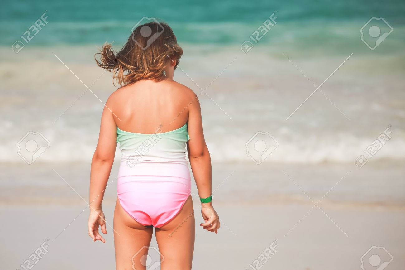 Little girl in bikini rear view Caucasian blond baby girl in green and pink swimsuit stands on the sea  coast, rear