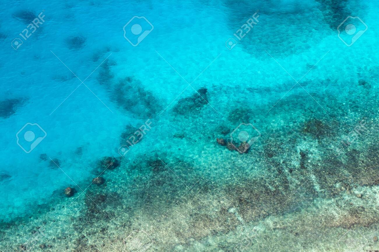 Persian Gulf, rocky seabed is under blue shallow water. Natural photo. Bird eye view - 144203328