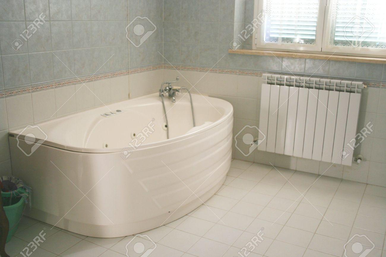 White salle de bain avec jacuzzi. Il est aussi une fenêtre et un radiateur.  La chambre est propre et prêt.