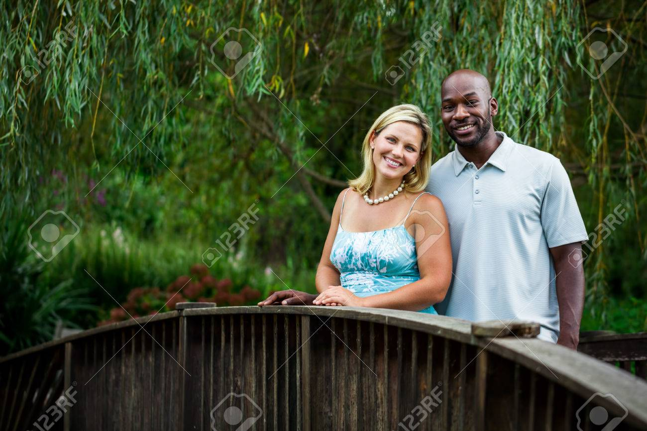 Beautiful interracial couple portrait at a park in summer standing on a bridge Stock Photo - 22476523