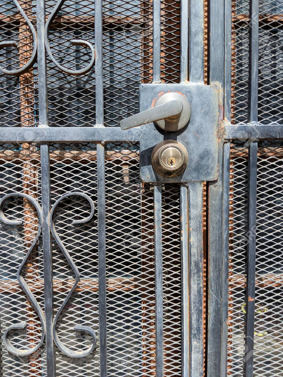 Handle And Key Lock On Wrought Iron Security Screen Door Stock Photo