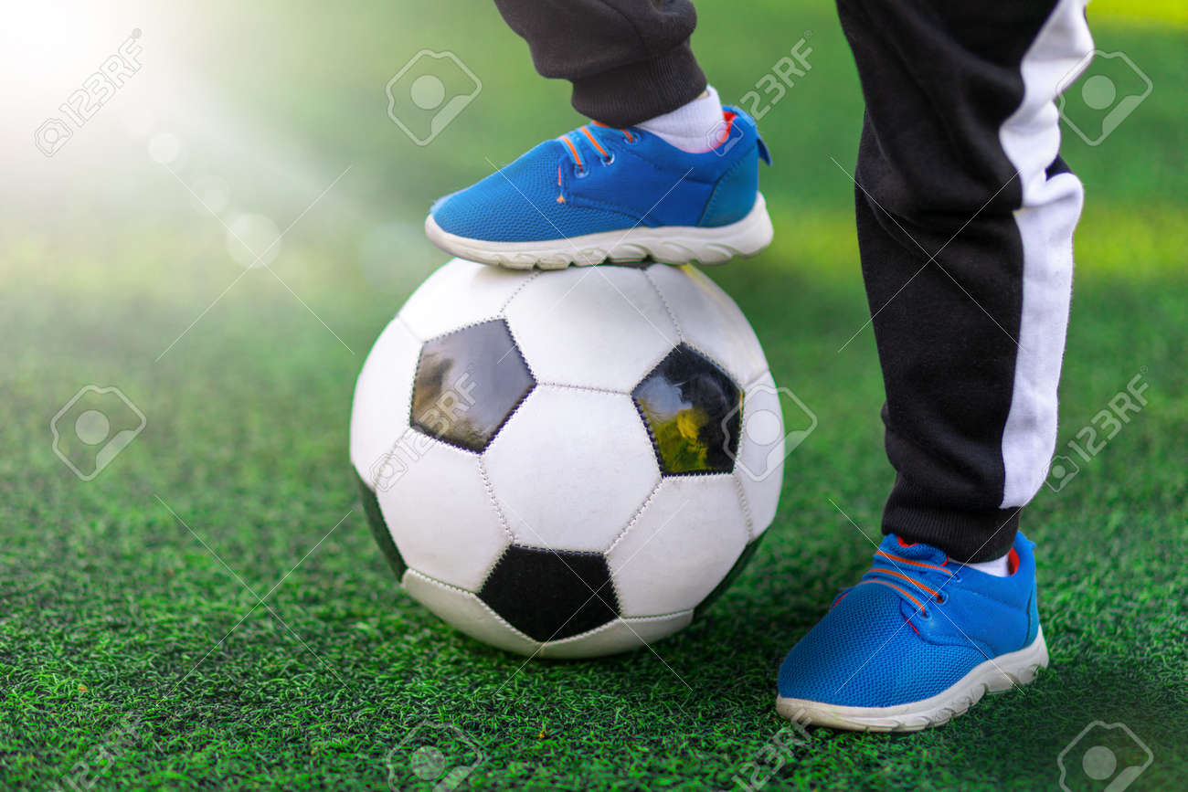 Children's foot of the winner in sports shoes sneaker stands on a soccer ball against a background of grass. Close-up street shot of game and training with victory. - 154845314