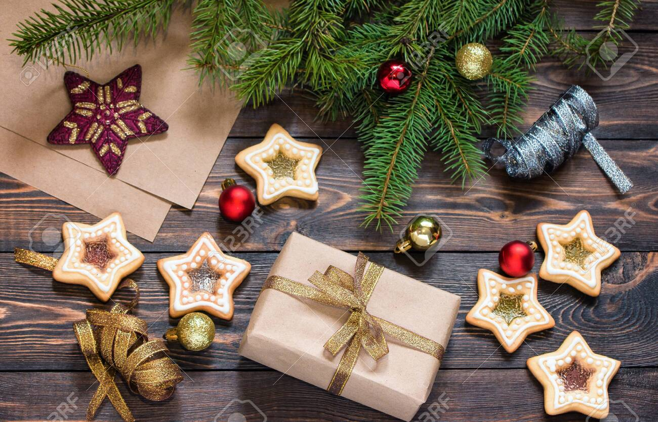 Christmas gift on wooden brown table with spruce branches, home-made cookies and Christmas tree toys. Top view. New Year and Christmas. - 133561298