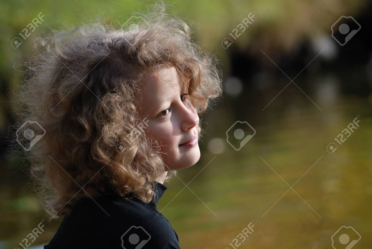 Pretty little girl sitting near a lake Stock Photo - 4339098