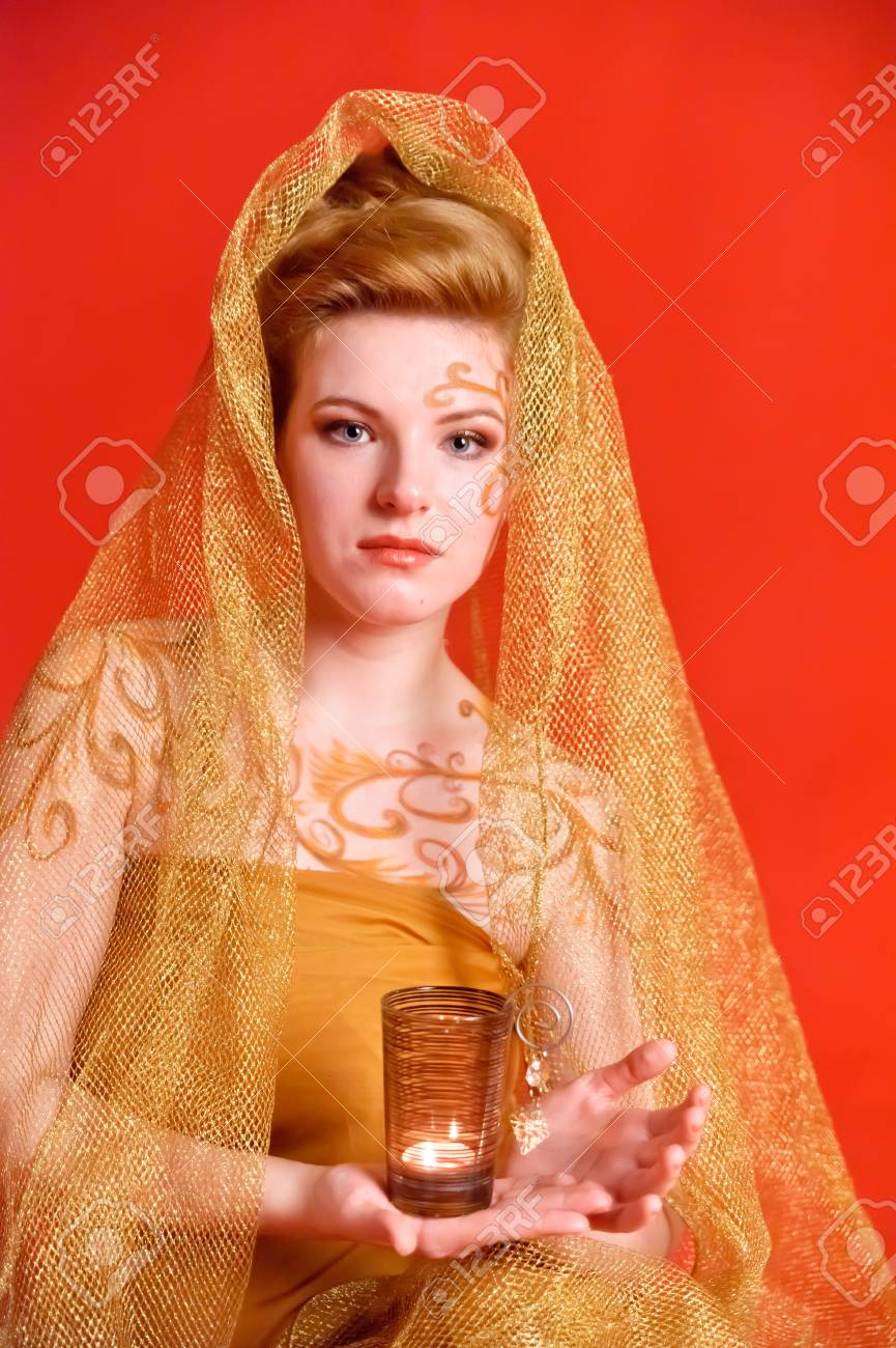 girl in a golden scarf with a candle Stock Photo - 9403768