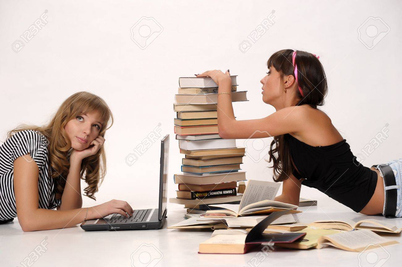 Women reading book and using laptop Stock Photo - 10078438