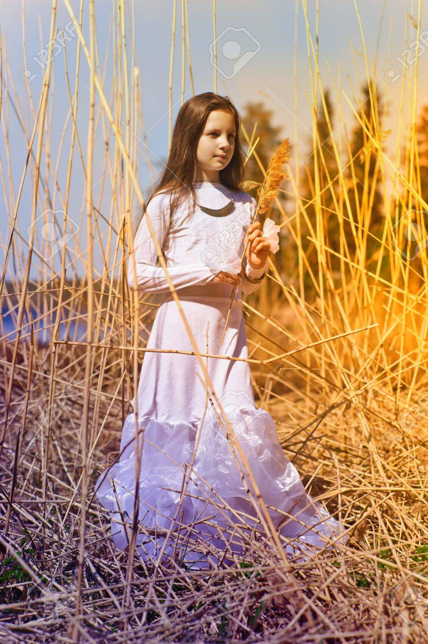 girl in white dress among the high dry grass Stock Photo - 10221557