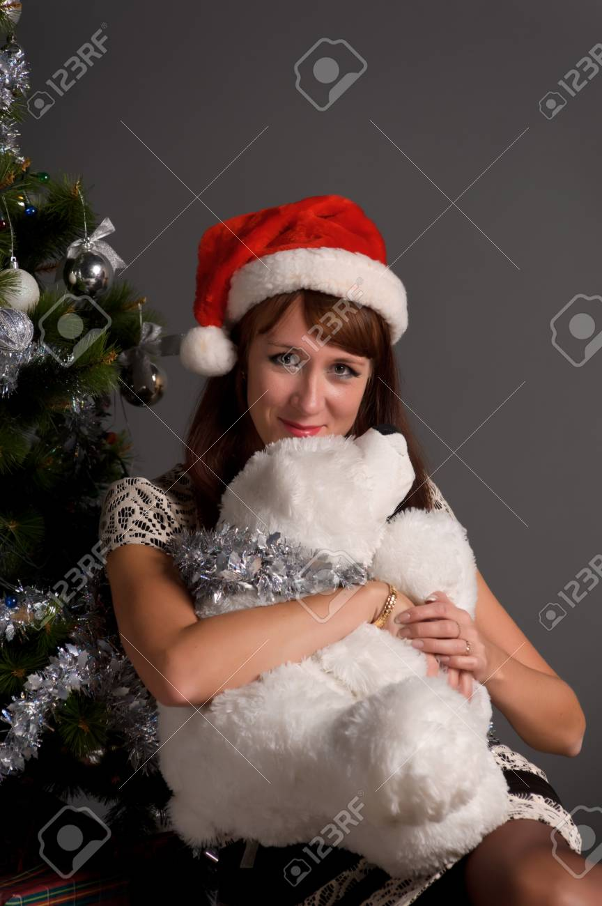 The young woman with a Christmas cap at a fur-tree Stock Photo - 11038159