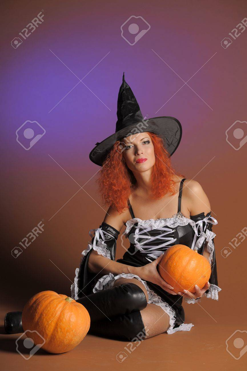 Beautiful red-haired witch with a pumpkin Stock Photo - 11190273