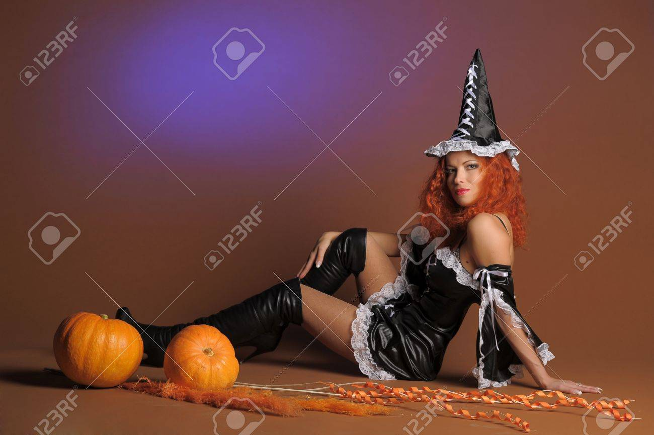 Beautiful red-haired witch with a pumpkin Stock Photo - 11190277