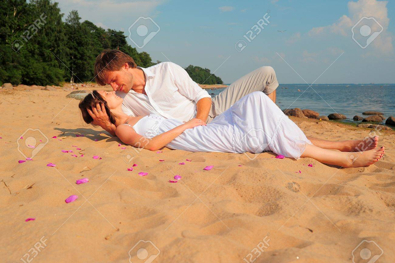 couple kissing while lying on the shore - 11489090