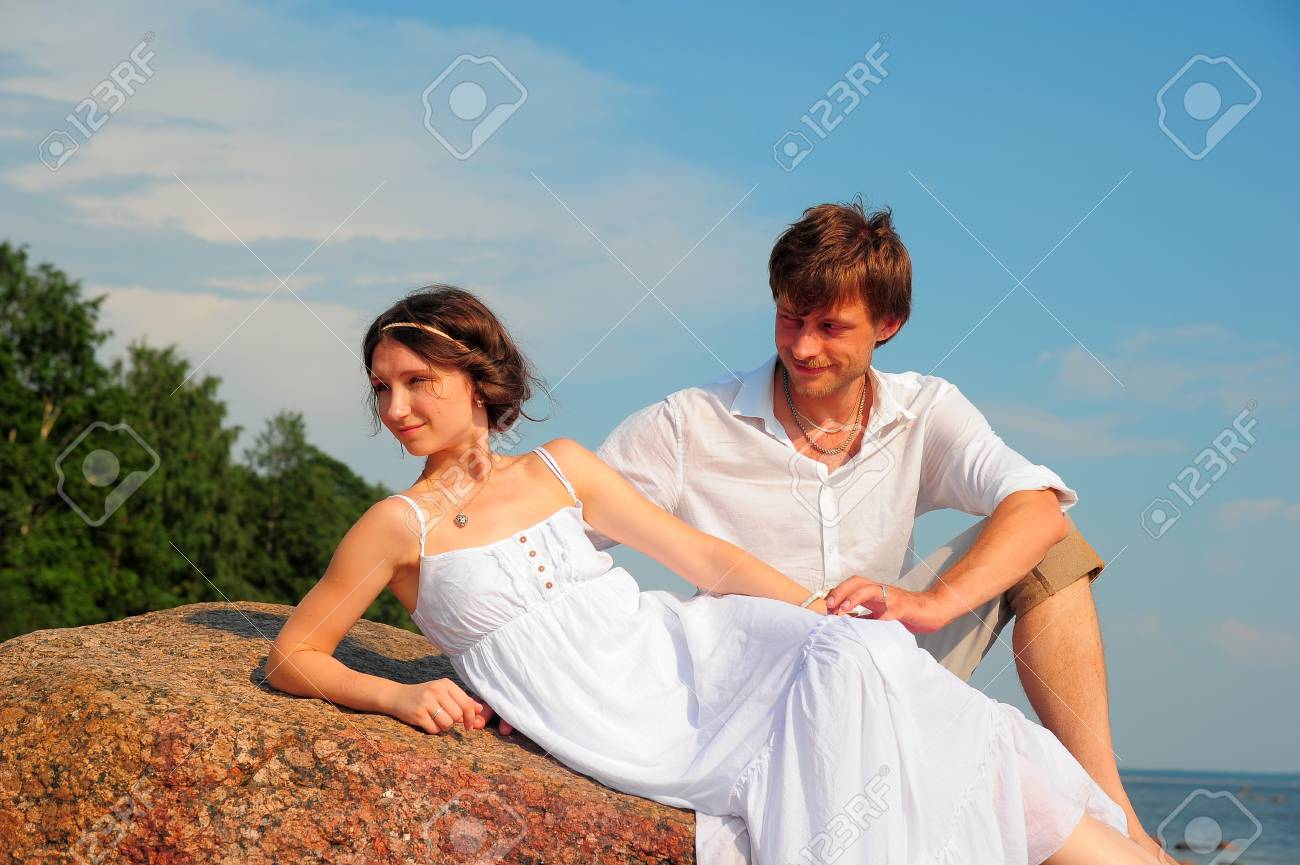 Smiling pair in white on the beach Stock Photo - 13305519