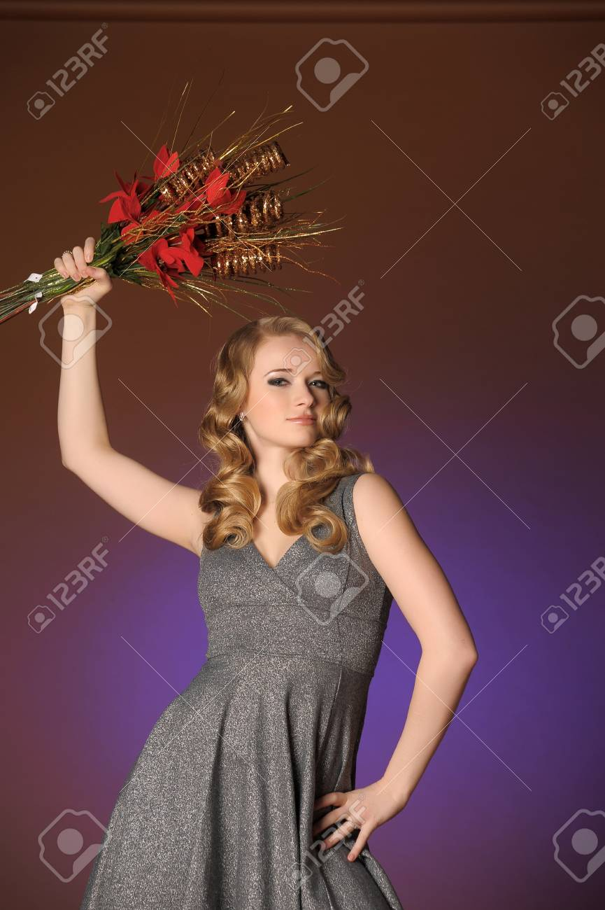 Vintage attractive blonde woman with a Christmas flower Stock Photo - 13572041