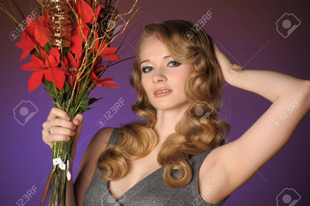 Vintage attractive blonde woman with a Christmas flower Stock Photo - 13571940