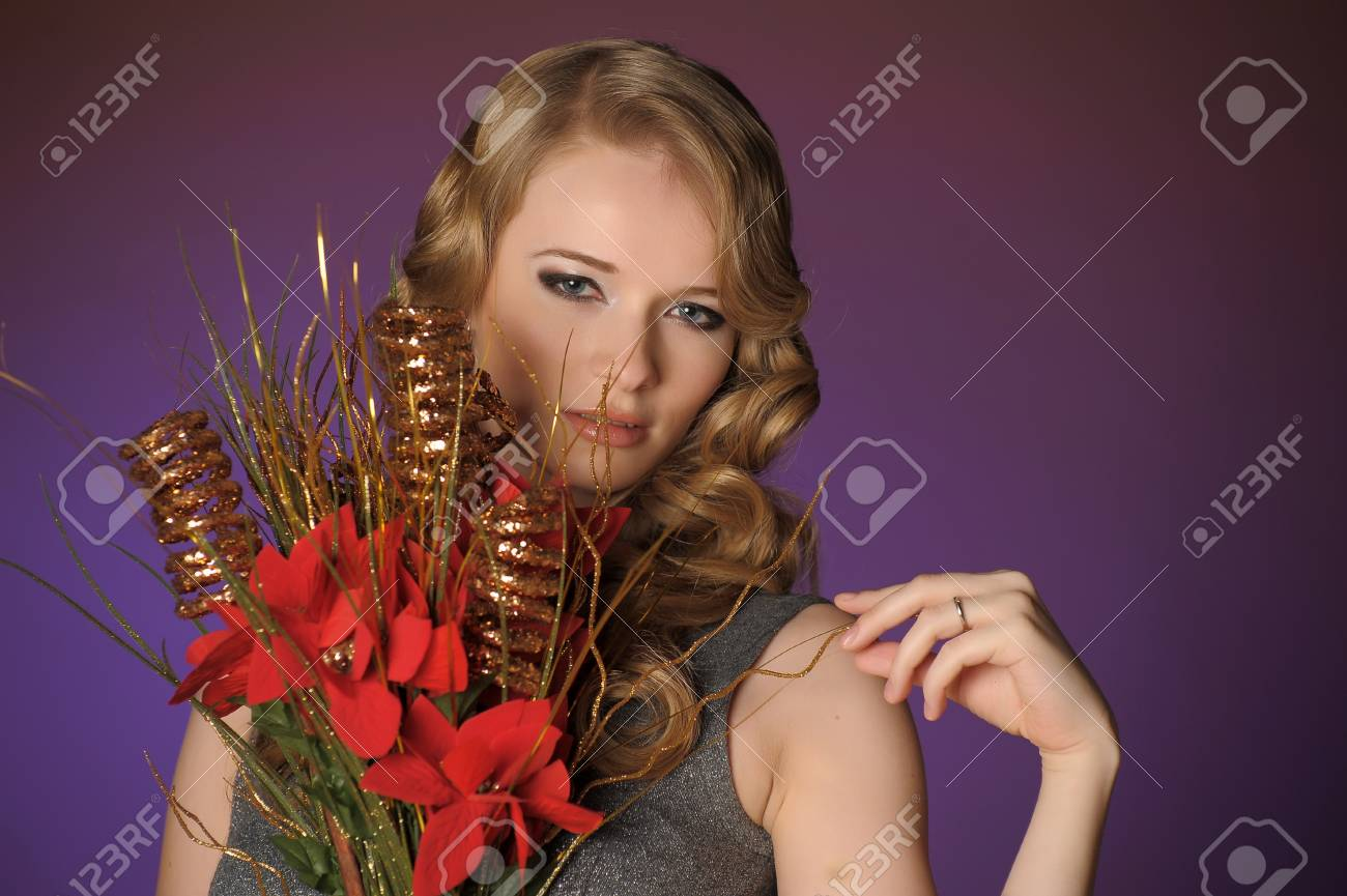 Vintage attractive blonde woman with a Christmas flower Stock Photo - 13572032