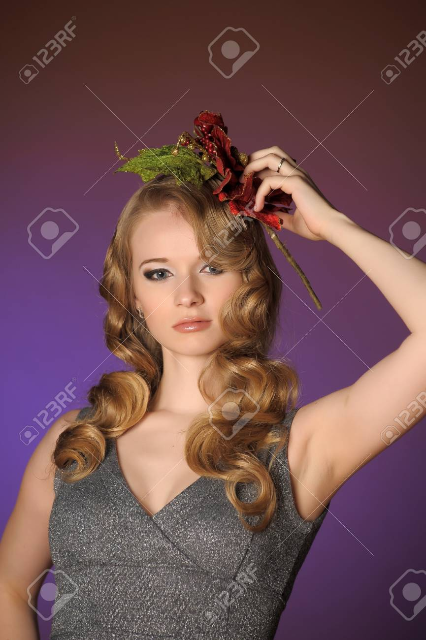 Vintage attractive blonde woman with a Christmas flower Stock Photo - 13572043