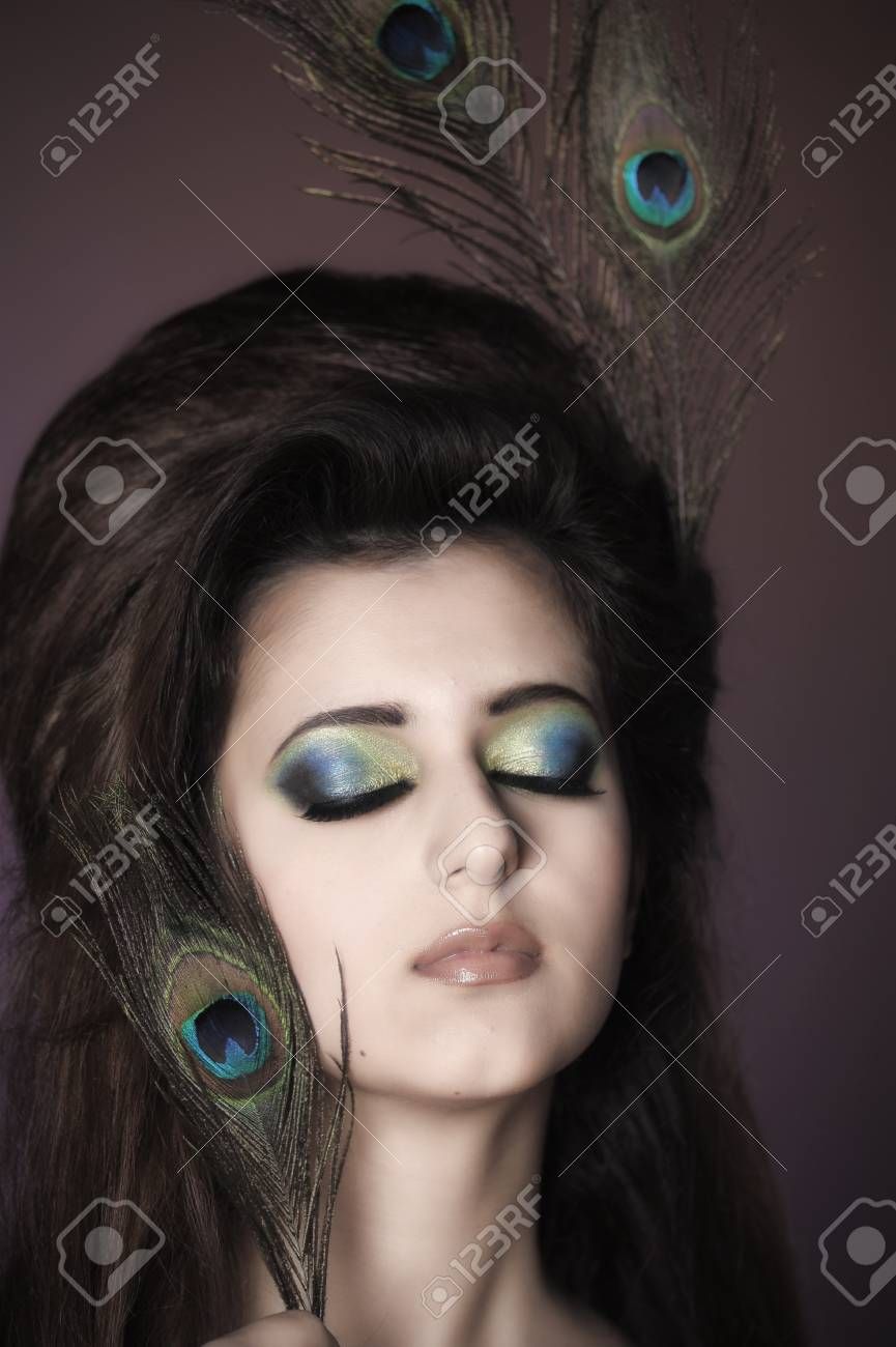 Portarit of beautiful young girl with peacock feather Stock Photo - 13280990