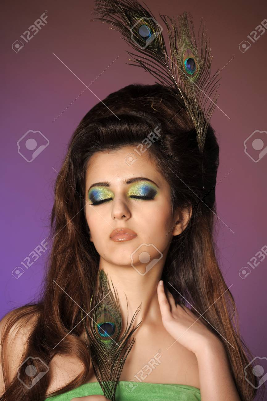Portarit of beautiful young girl with peacock feather Stock Photo - 13281356