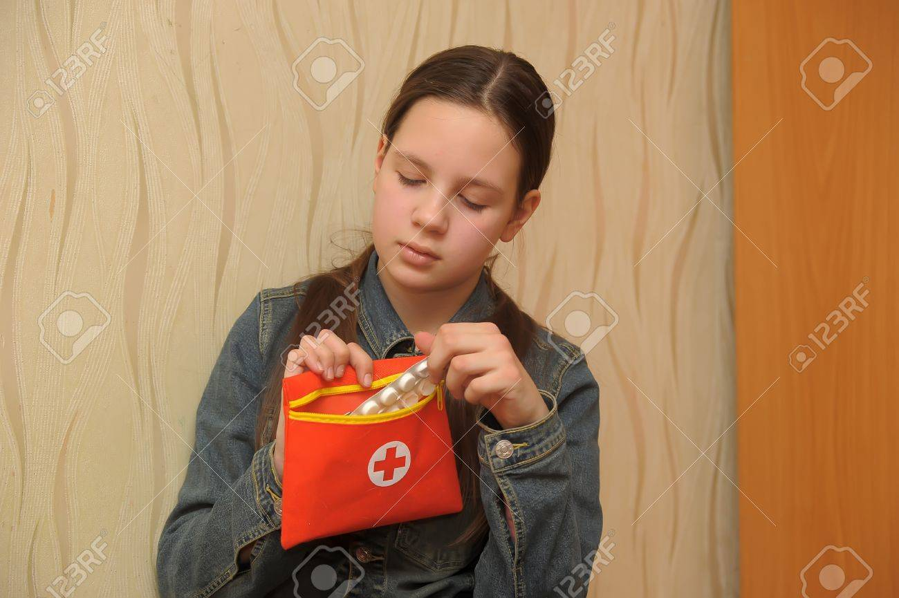 young woman  teenage girl  decides wether to take pills Stock Photo - 12387120