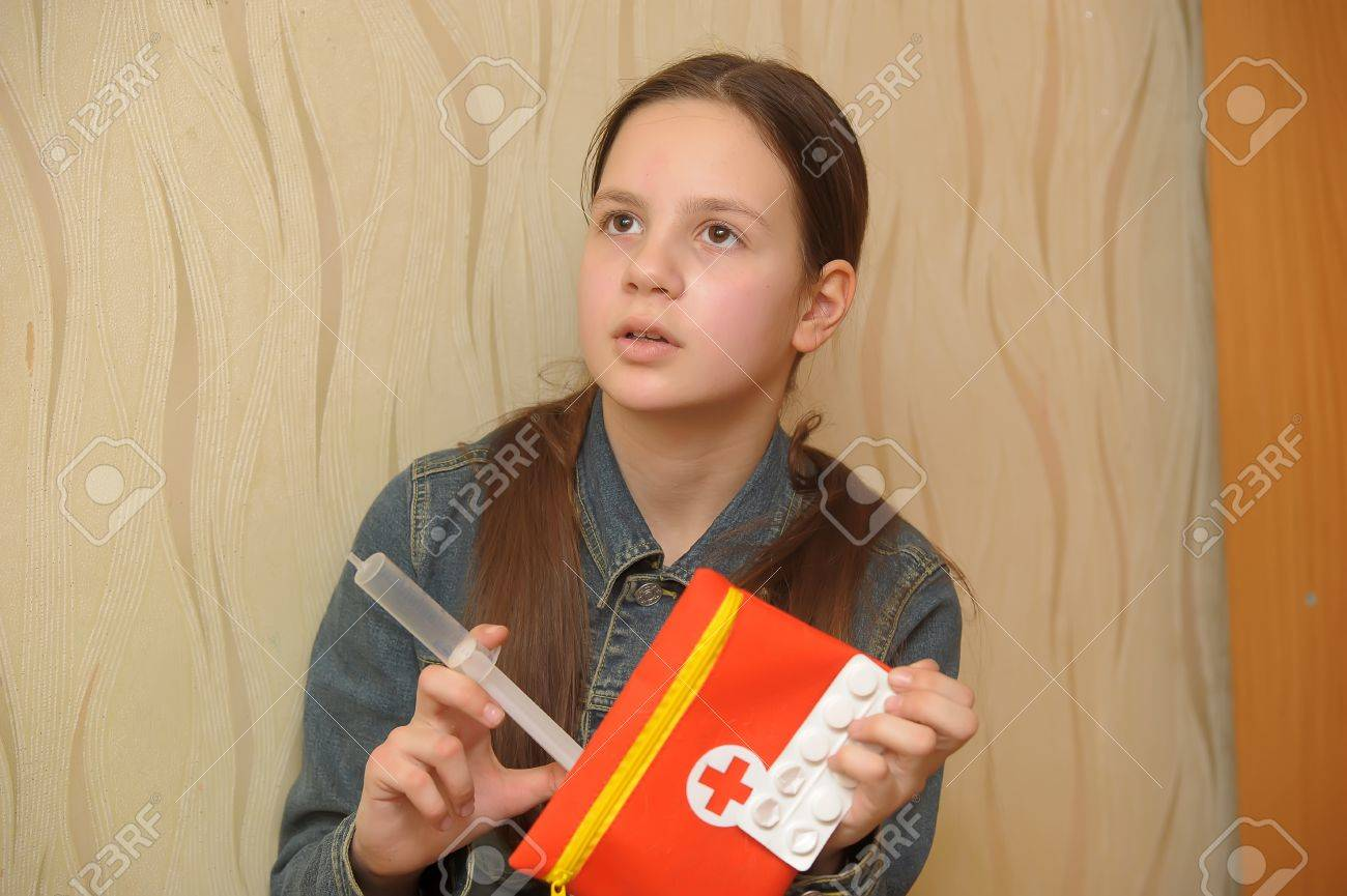 The girl the teenager with tablets and a syringe in hands Stock Photo - 12387118