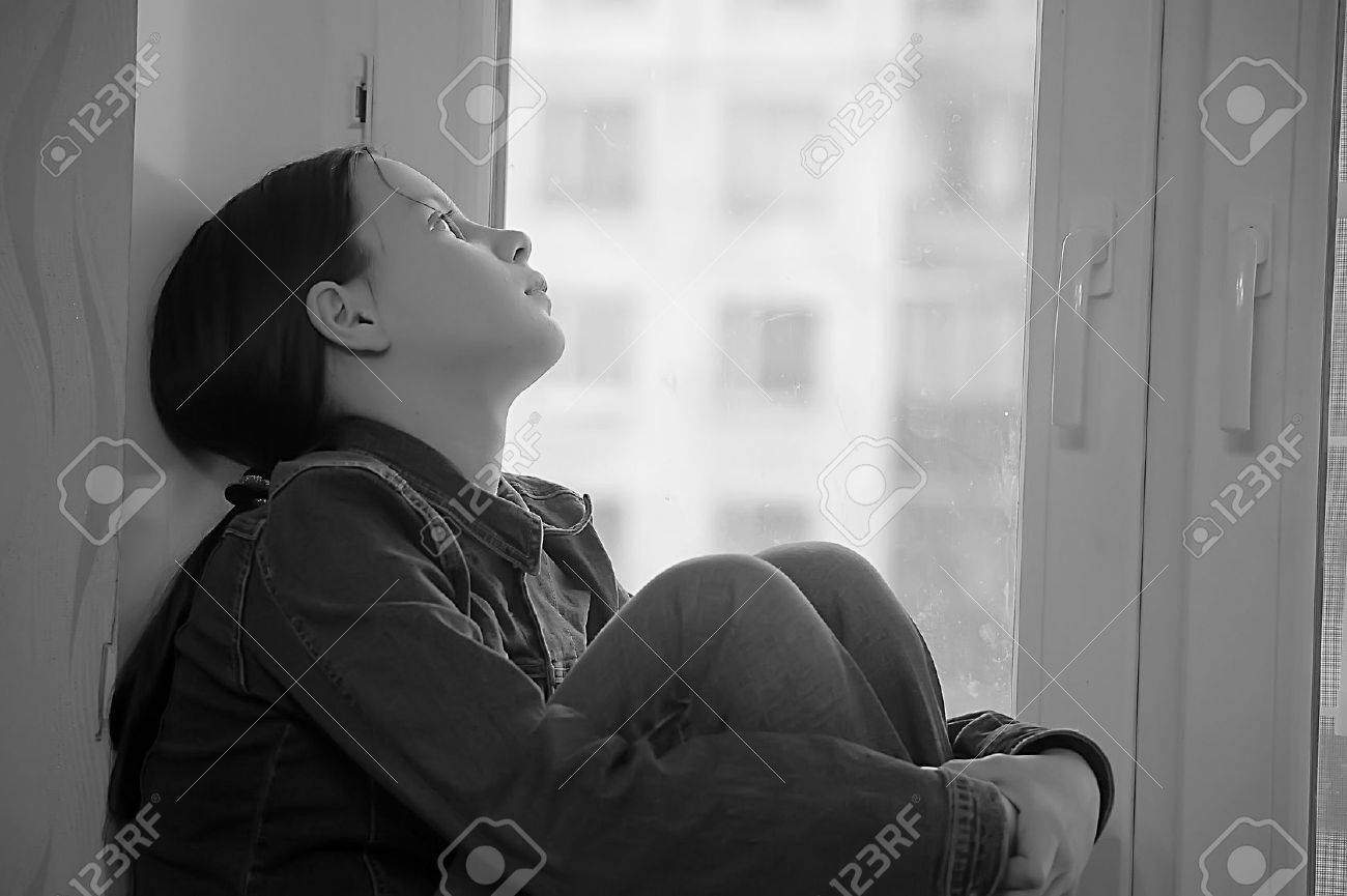 The sad girl the teenager at home on a window sill Stock Photo - 12443034