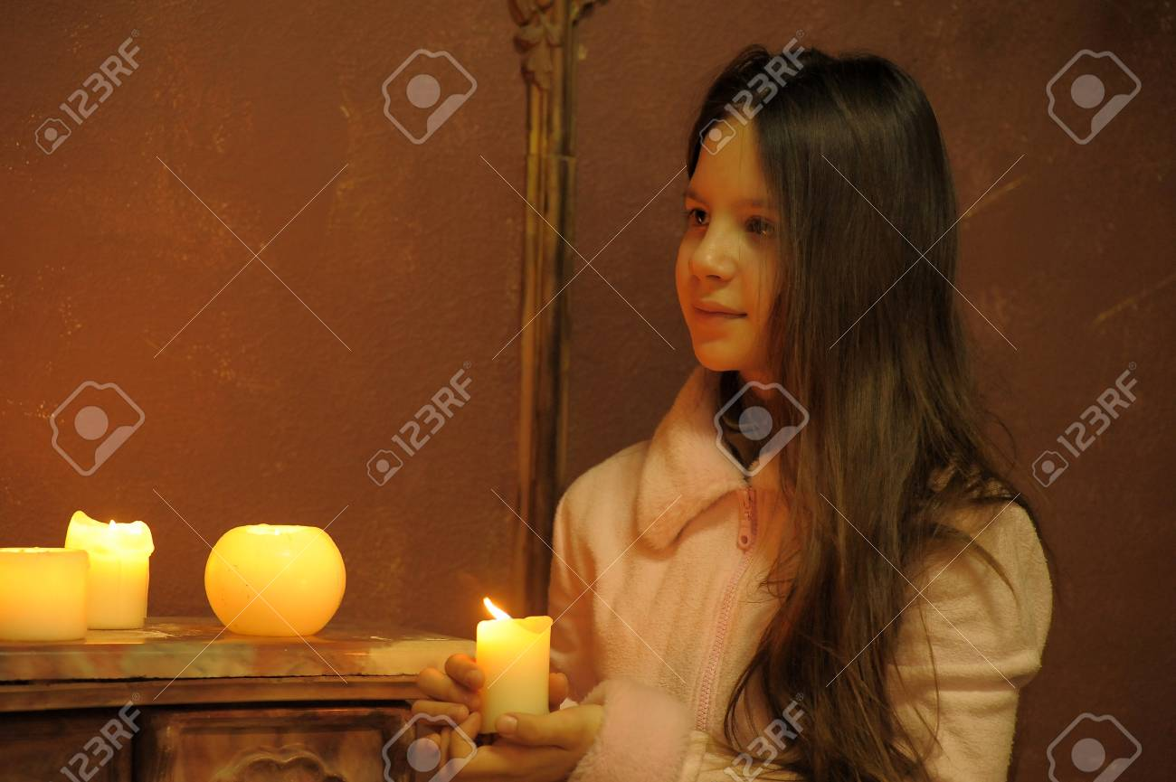 The girl the teenager at a fireplace with candles Stock Photo - 12414308