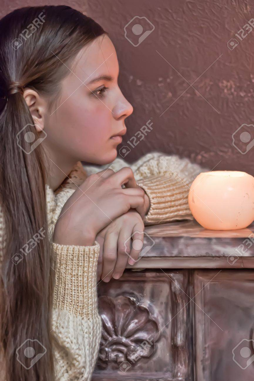 The girl the teenager at a fireplace with candles Stock Photo - 12466161